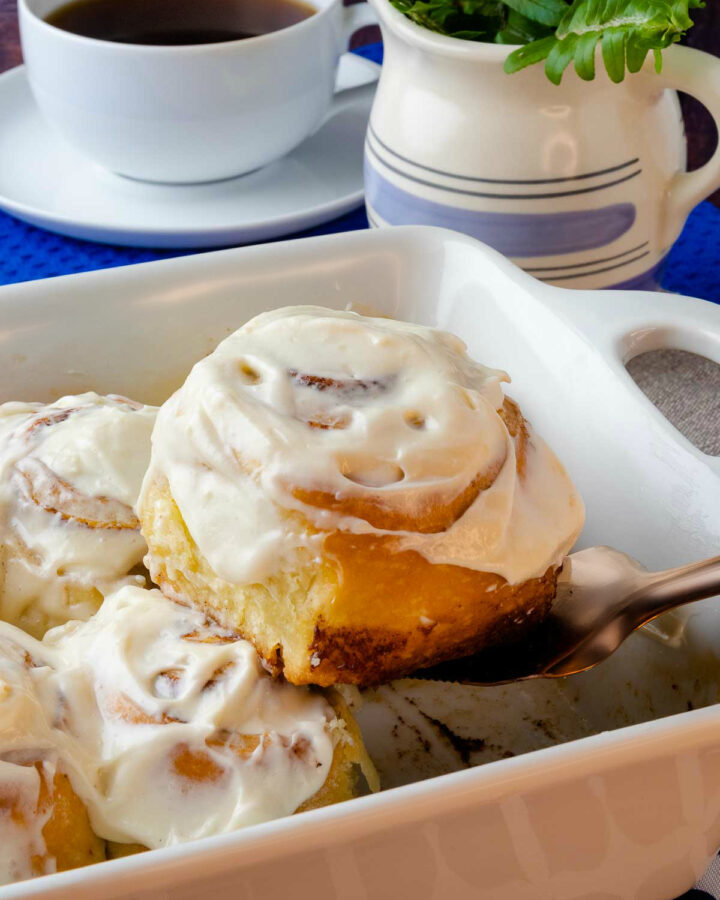Easy to make Cinnamon Rolls in a pan being scooped with a copper utensil served with a cup of coffee.