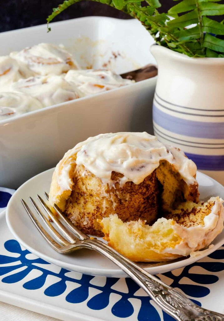 Easy Cinnamon Rolls on a plate with icing cut with a fork.