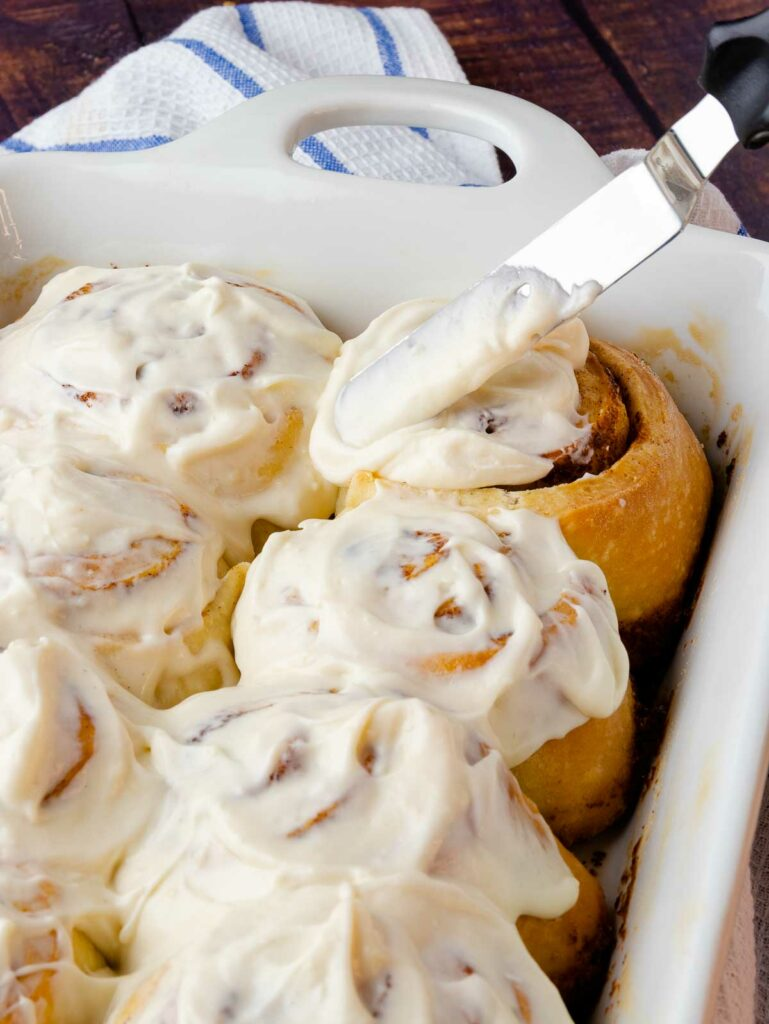 Easy Cinnamon Rolls in a white pan with a knife icing the rolls.