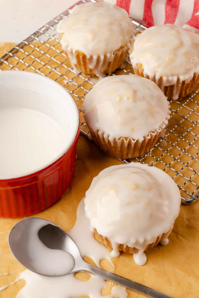Glazed Eggnog Muffins on a cooling rack and napkin.