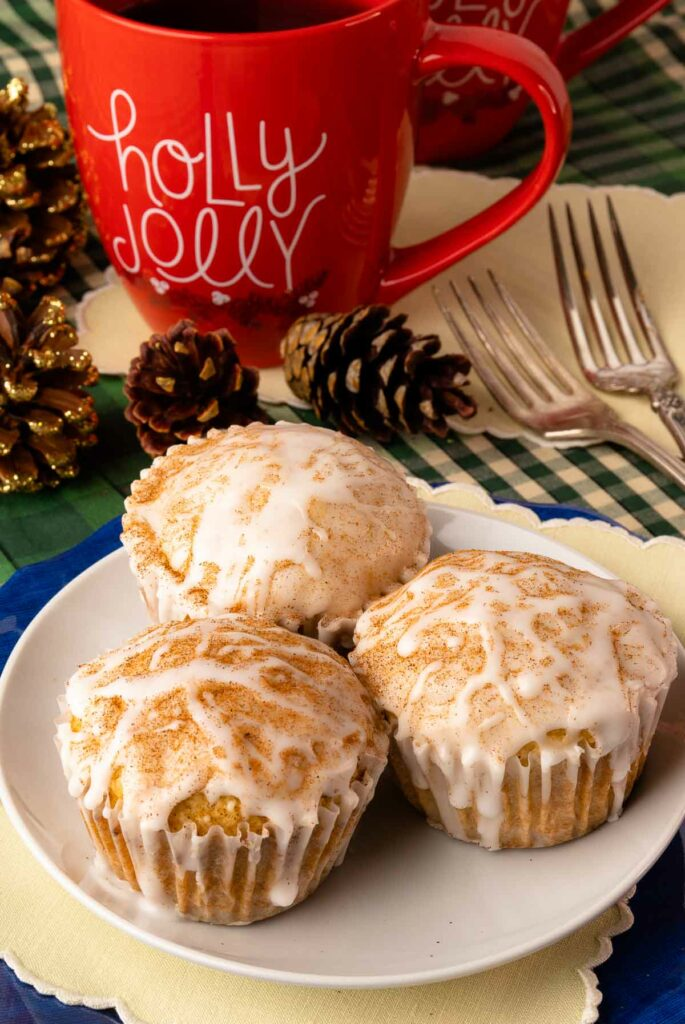 Eggnog Muffins on a white plate glazed with eggnog and sprinkled with cinnamon.