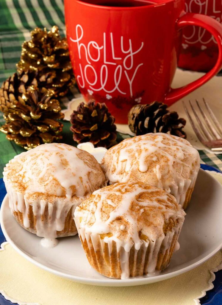 Eggnog Muffins on a white plate with a red mug and pinecones on the table.