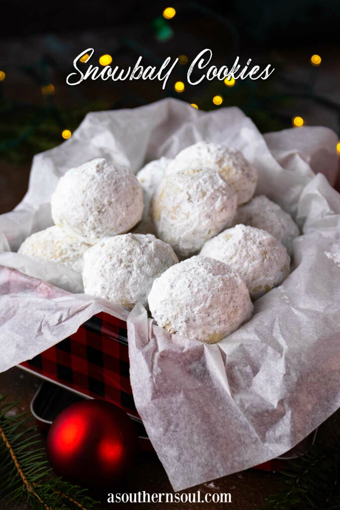 Snowball Cookies in a metal tin with Christmas decorations image for Pinterest.