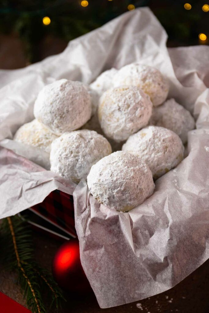 Snowball Cookies in a metal tin under the Chrismas tree.
