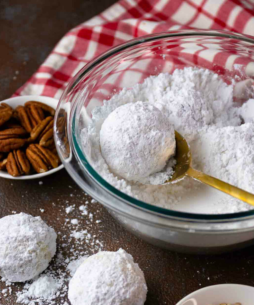 Snowball Cookies dipped in powdered sugar made with chopped pecans.