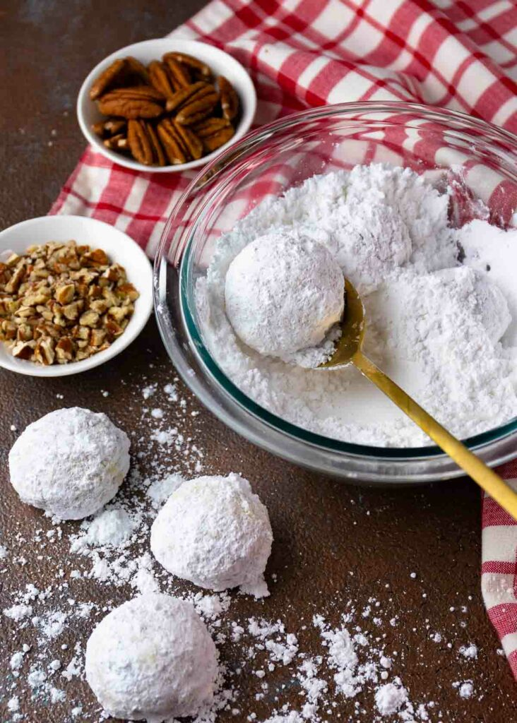 Snowball Cookies with pecans and powdered sugar in a bowl.