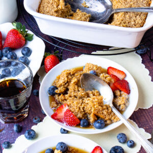 Baked Oatmeal on plates with maple syrup, blueberries and strawberries.