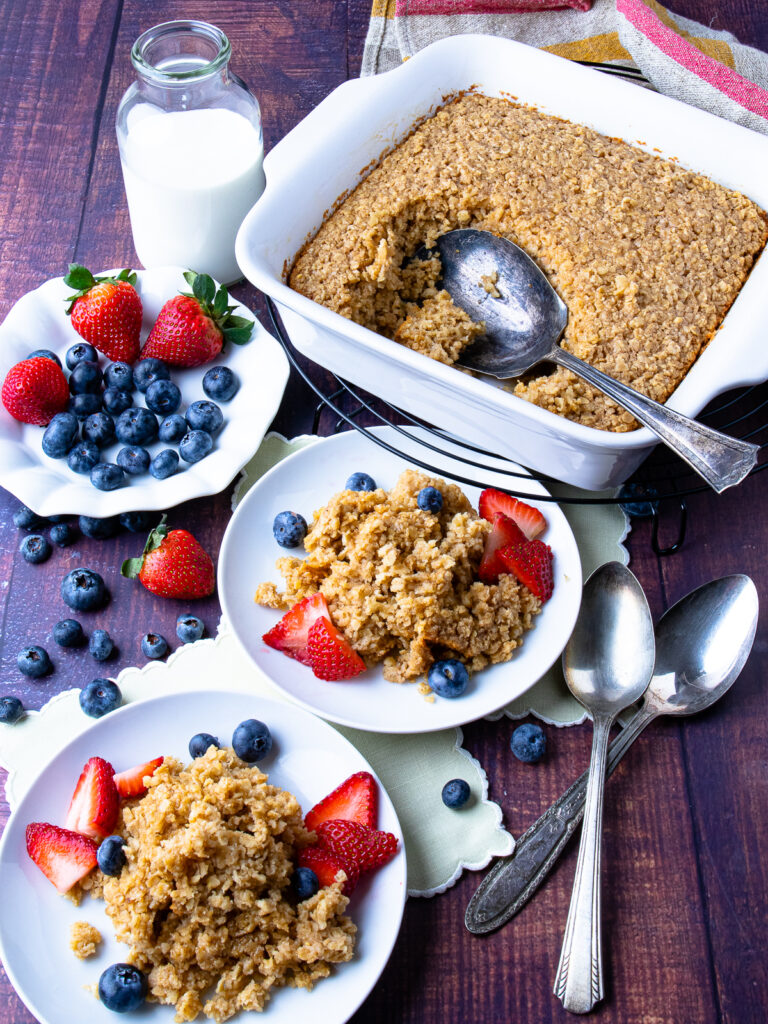 Maple Cinnamon Baked Oatmeal in a pan with fruit and milk.