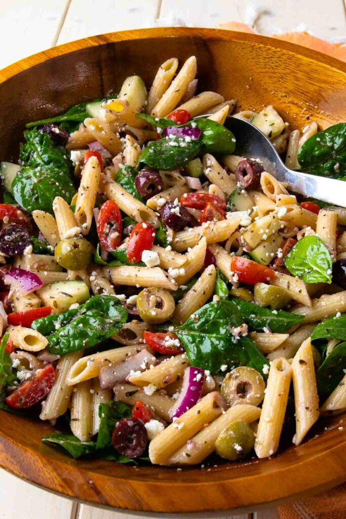 Large wooden bowl with metal spoon full of Mediterranean Pasta Salad.