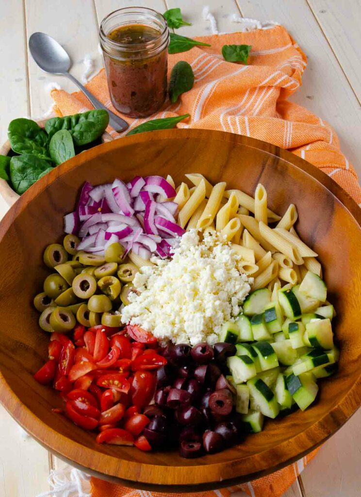 Pasta, olives, tomatoes, onions and cucumbers in wooden bowl for Mediterranean Pasta Salad.