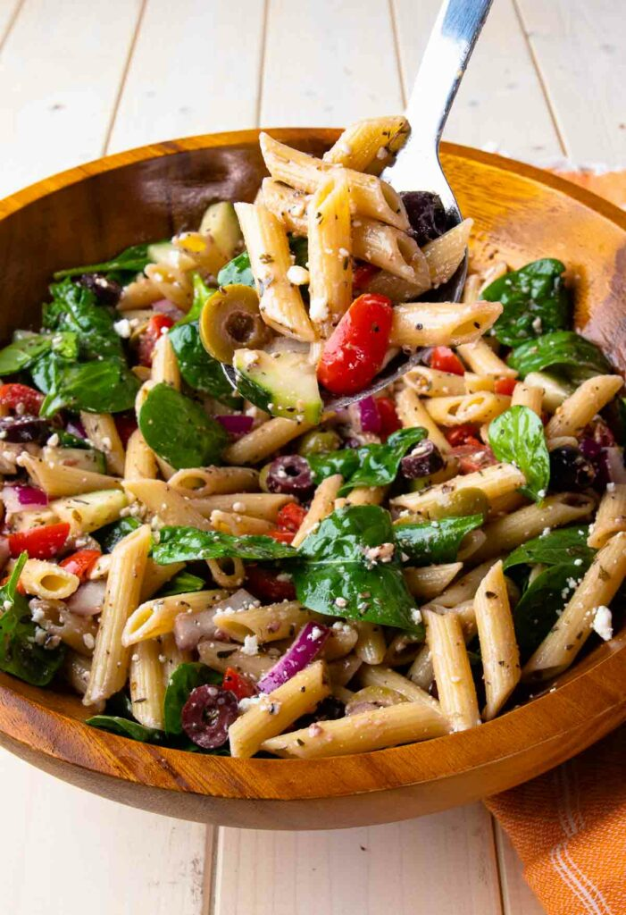 Mediterranean Pasta Salad on a large metal spoon being served for lunch.