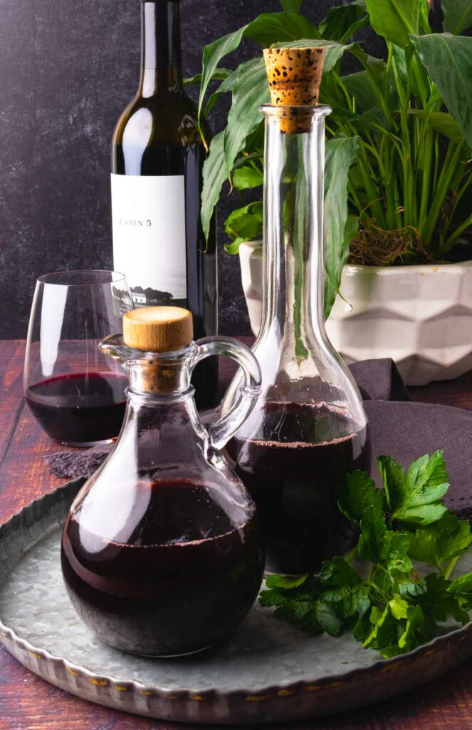 Two glass bottles of homemade red wine vinegar on a metal tray with greenery.