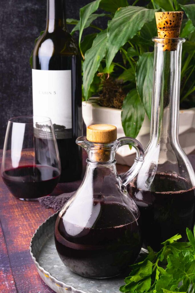 How to make red wine vinegar showing 2 glass bottles and greenery.