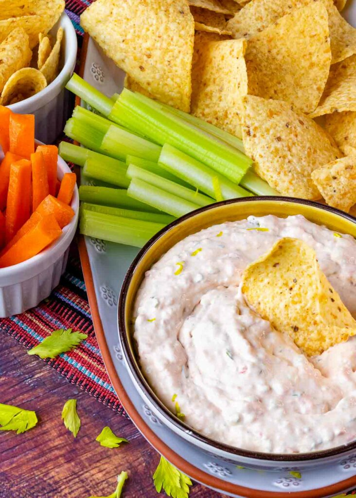 Bowl of Southwest Ranch Dip on a platter with celery sticks and tortilla chips.