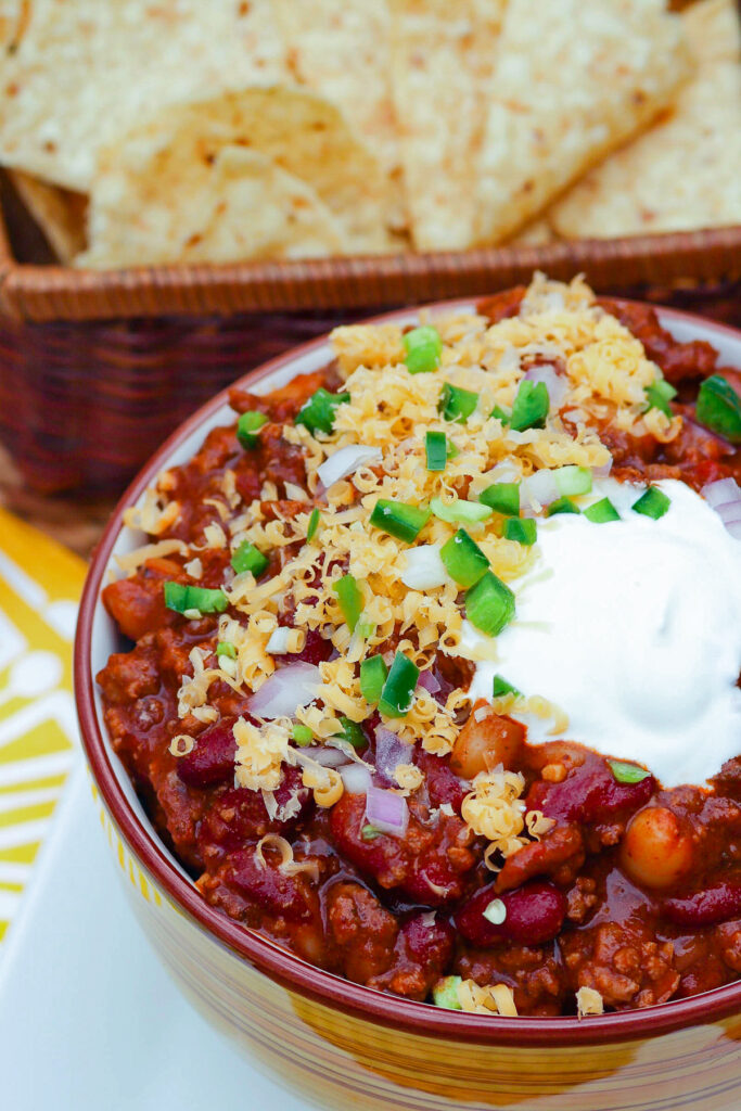Bloody Mary Chili in a yellow bowl topped with sour cream, cheese and jalapenos.