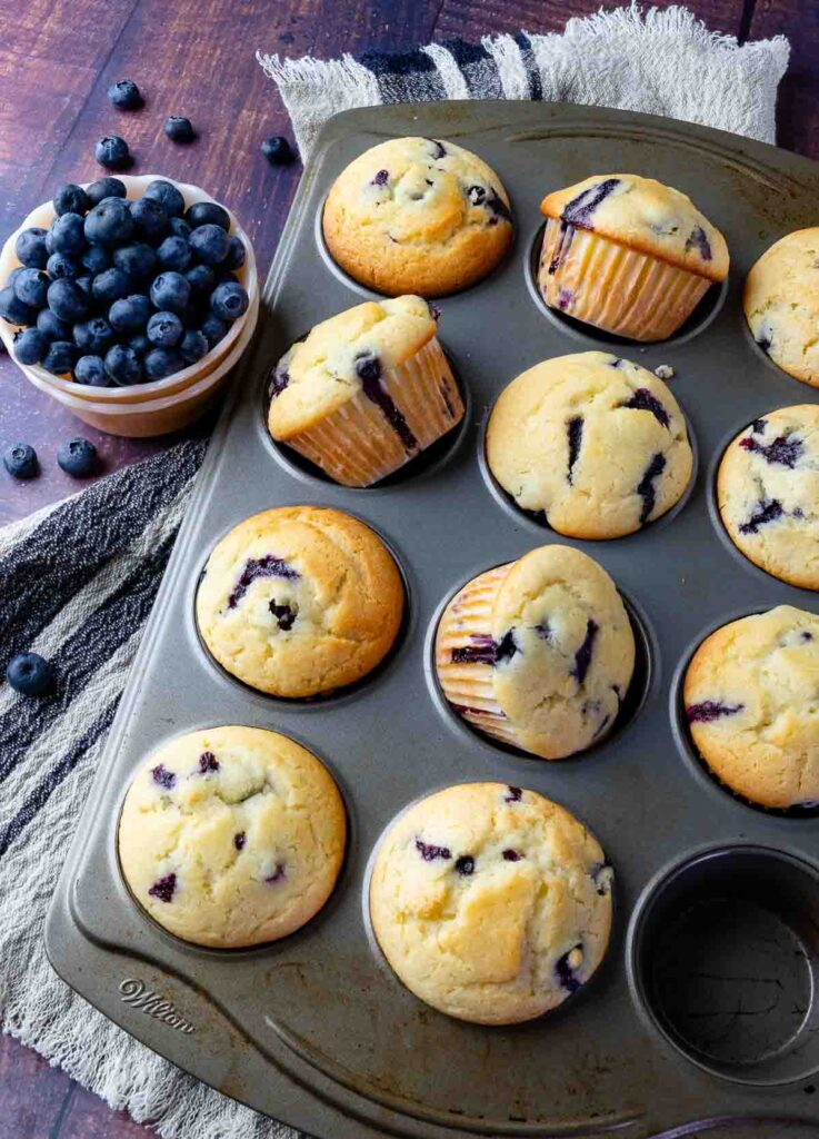 Blueberry Sour Cream Muffins in a muffin pan with fresh blueberries in a bowl.