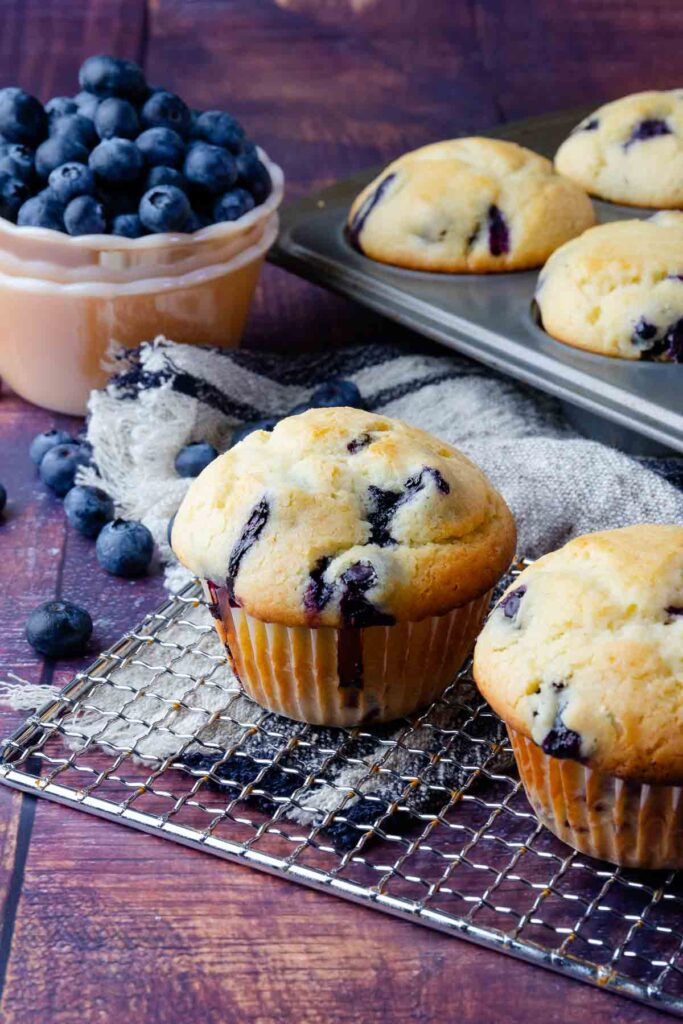 Blueberry Sour Cream Muffins on a cooling rack with fresh blueberries in a bowl.