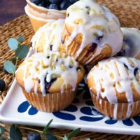 Blueberry Sour Cream Muffins With Lemon Glaze on a plate with fresh blueberries.