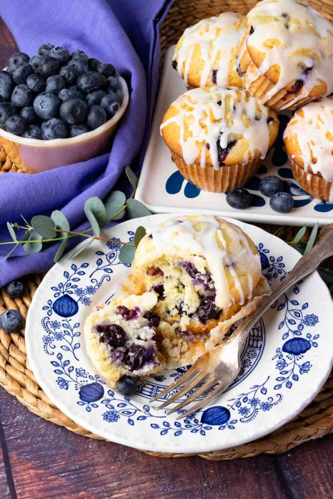 Blueberry Sour Cream Muffins With Lemon Glaze on a blue and white plate with fork.