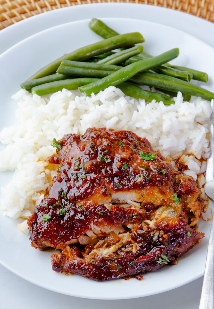 Sliced Crock Pot Chicken Thigh with rice and green beans on a white plate.