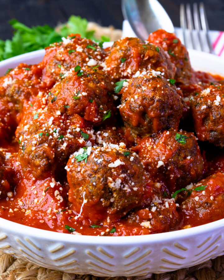 Homemade meatballs in tomato sauce in a white bowl with parsley on top.
