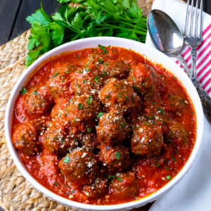 Homemade Meatballs in a white bowle with a napkin, spoon and fork.