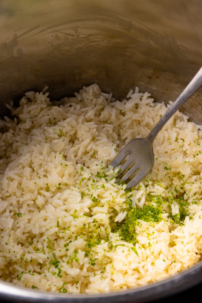 Instant Pot Coconut Rice with lime zest in a pot with fork.