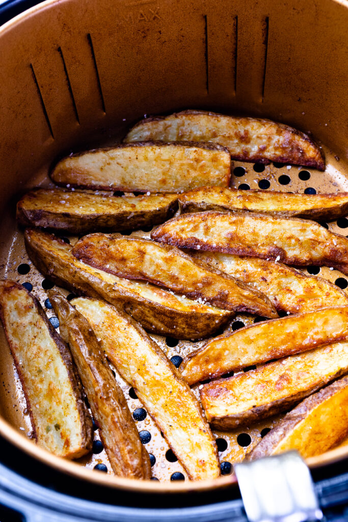 Potato Wedges cooked in the basket of the air fryer.