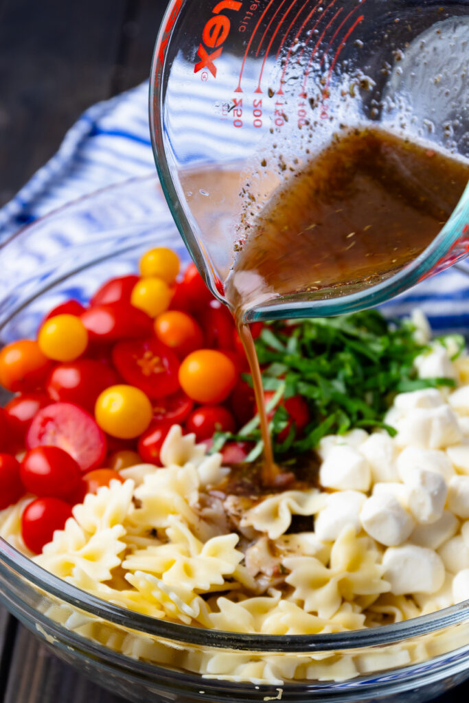 Balsamic herb dressing poured over fresh ingredients make Caprese Pasta Salad so delicious.