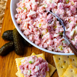 Ham Salad in a bowl with a spoon and pickles and crackers