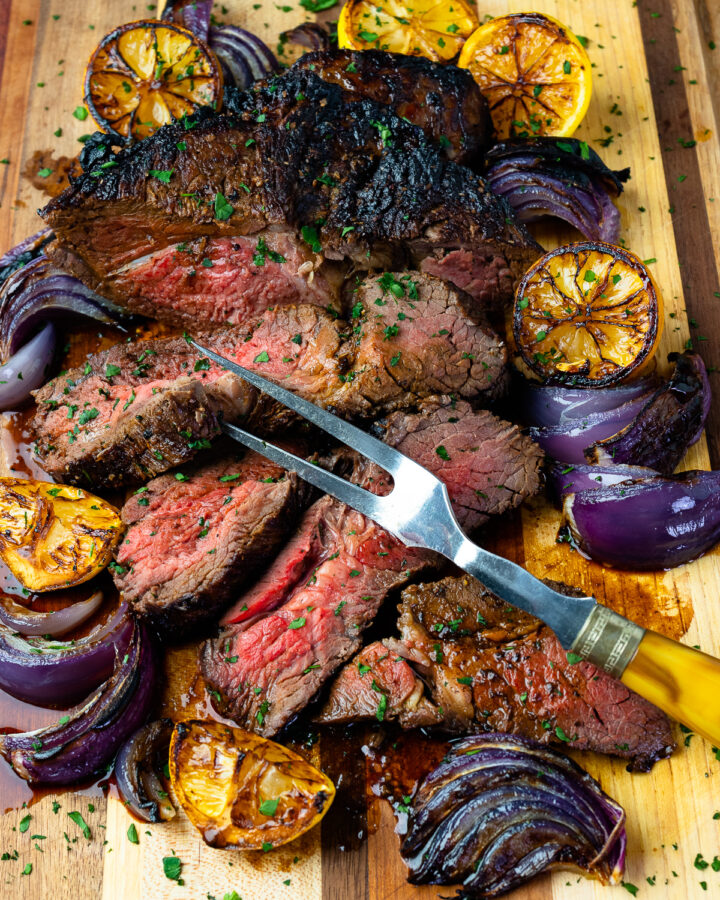 Marinated London Broil with lemons and onions with a serving fork on a wooden board.