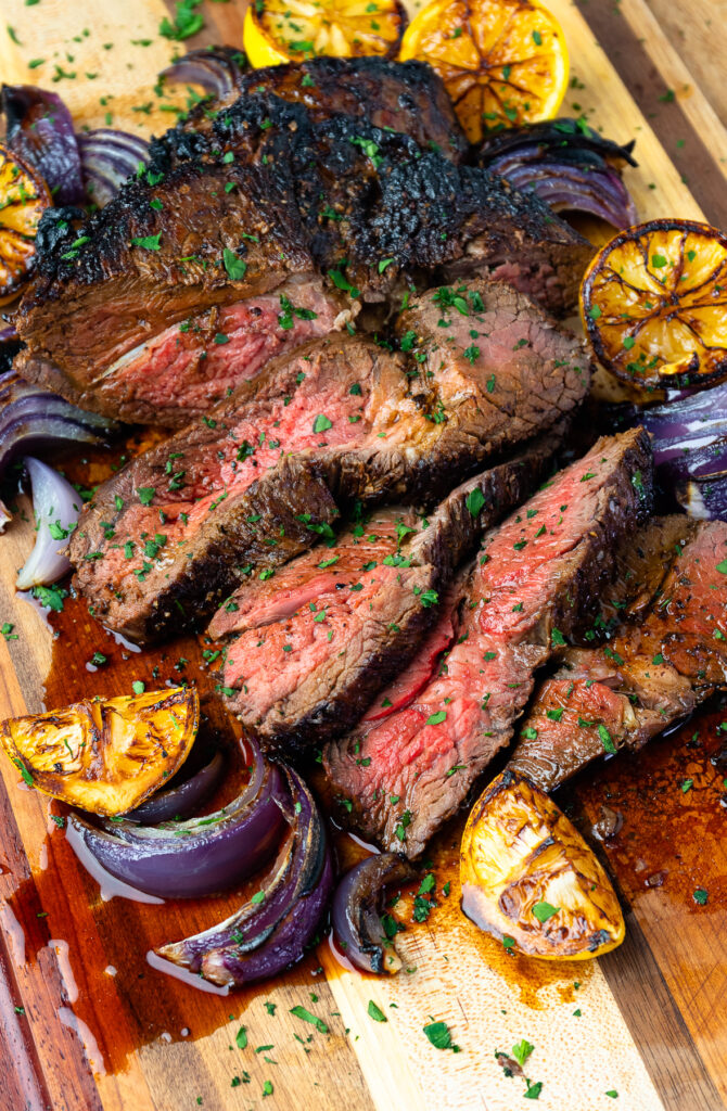 Marinated London Broil on a cutting board with seared lemons and onions.