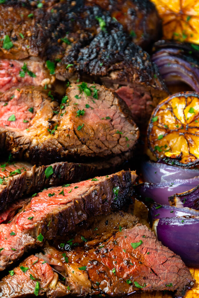 Close up of marinated london broil with seared lemons and onions.