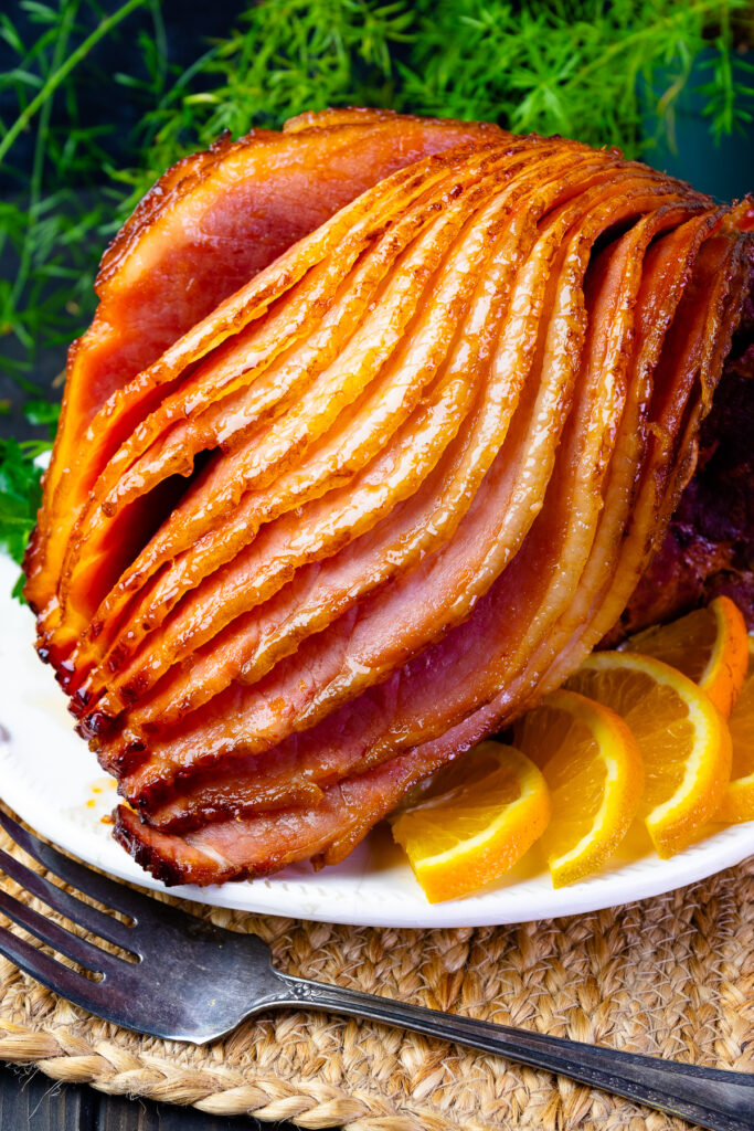 Orange and Pepper Jelly Glazed ham on a platter with fresh oranges for the holiday meal.