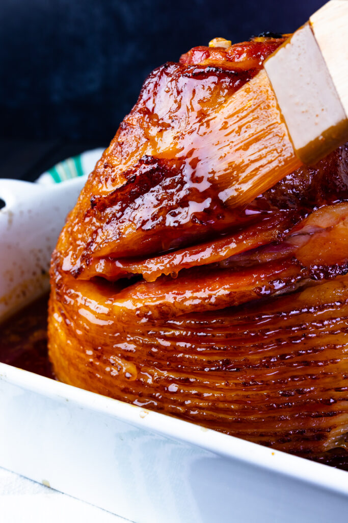 Orange and Red Pepper Jelly Glazed Ham is baked in a baking dish is juicy and sweet.