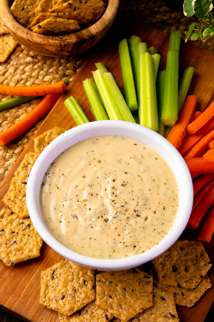 Bowl of Garlic Herb Tahini Dressing with carrots, celery and crackers.