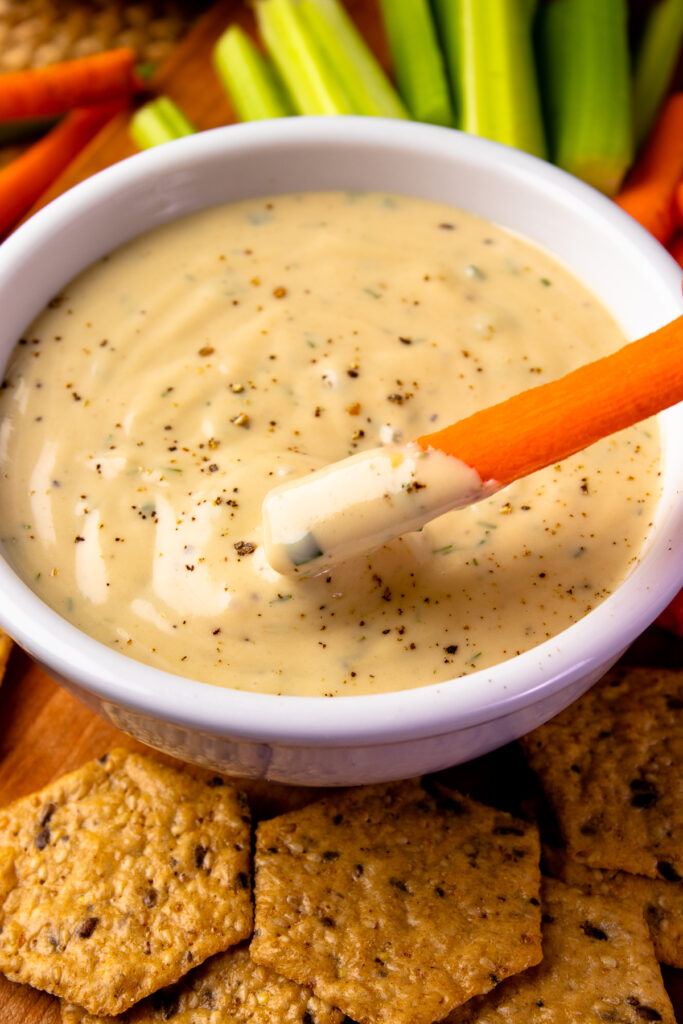 White bowl with Garlic Herb Tahini Dressing and Dip with a carrot.
