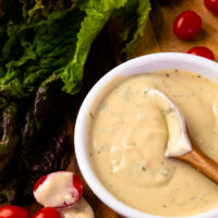 Spoon in a bowl of Garlic Herb Tahini Dressing and Dip with lettuce and tomatoes