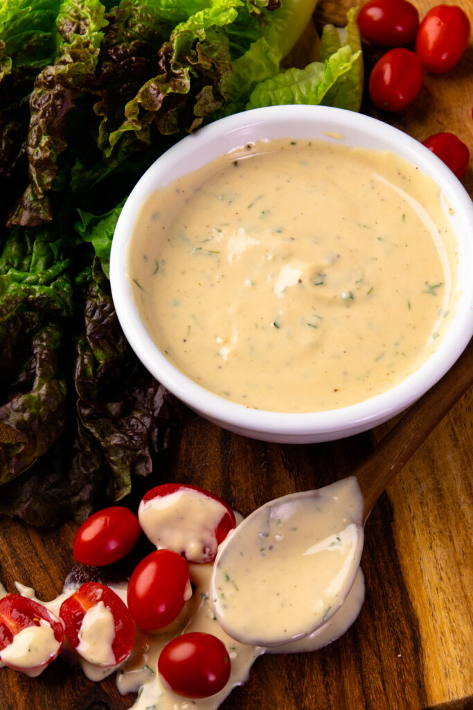 Garlic Herb Tahini Dressing and Dip in a bowl along with lettuce and tomatoes