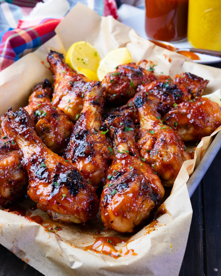 Grilled BBQ Chicken Legs with sauce and lemons.