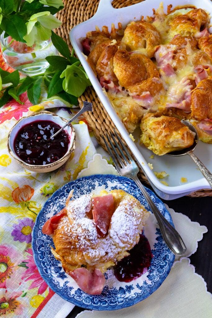 Croissant Breakfast Casserol served with strawberry ham and posdered sugar.