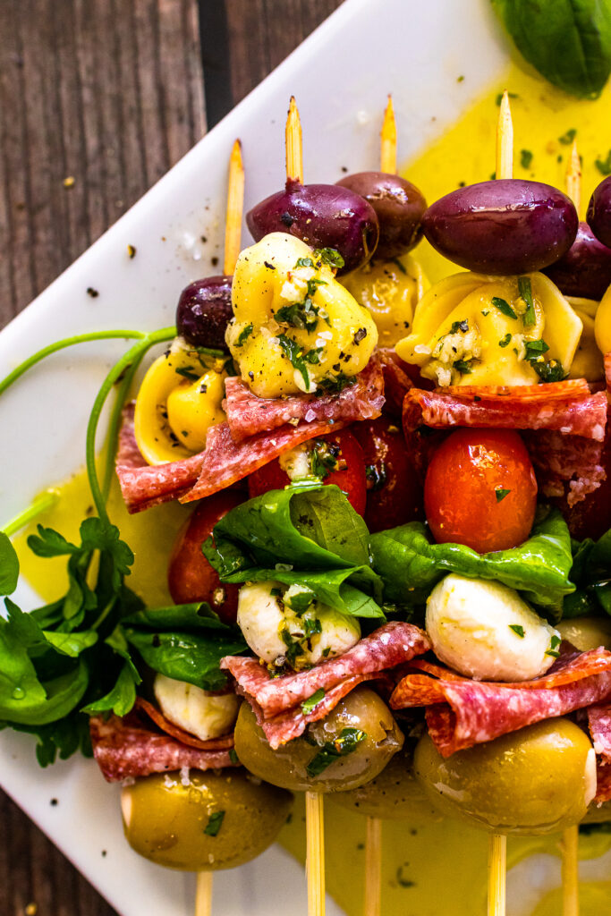 Antipasto Skewers served on a white plate drizzled with homemade dressing.