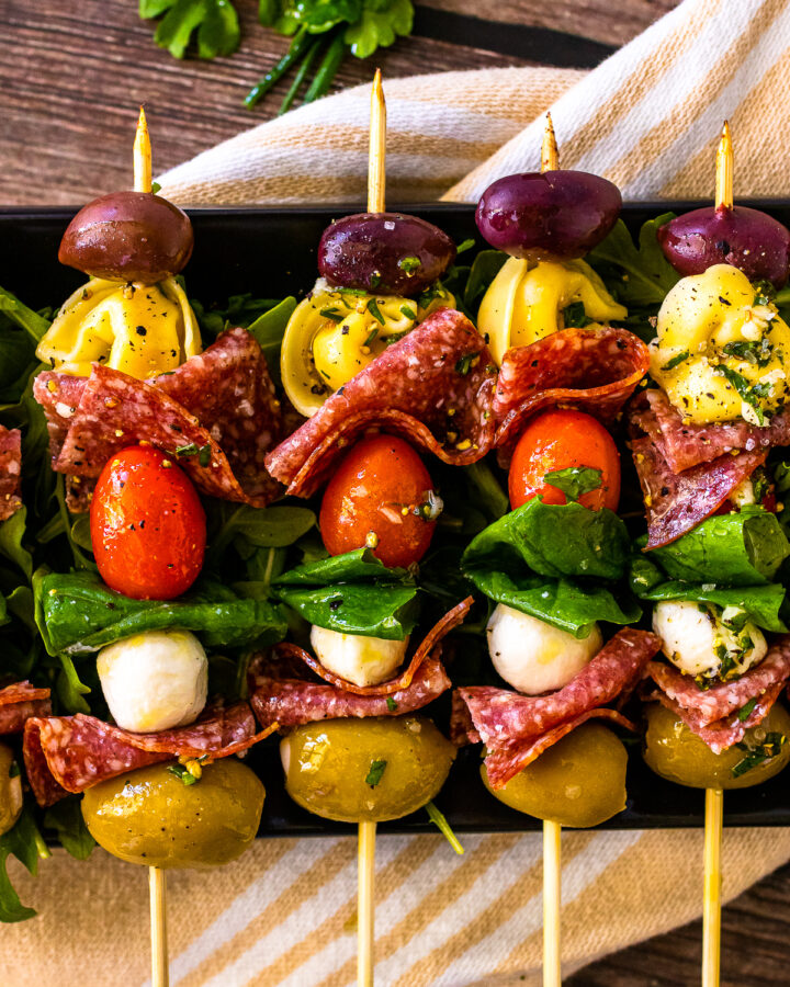 Antipasto skewers with olives and pasta lined up on a serving platter.