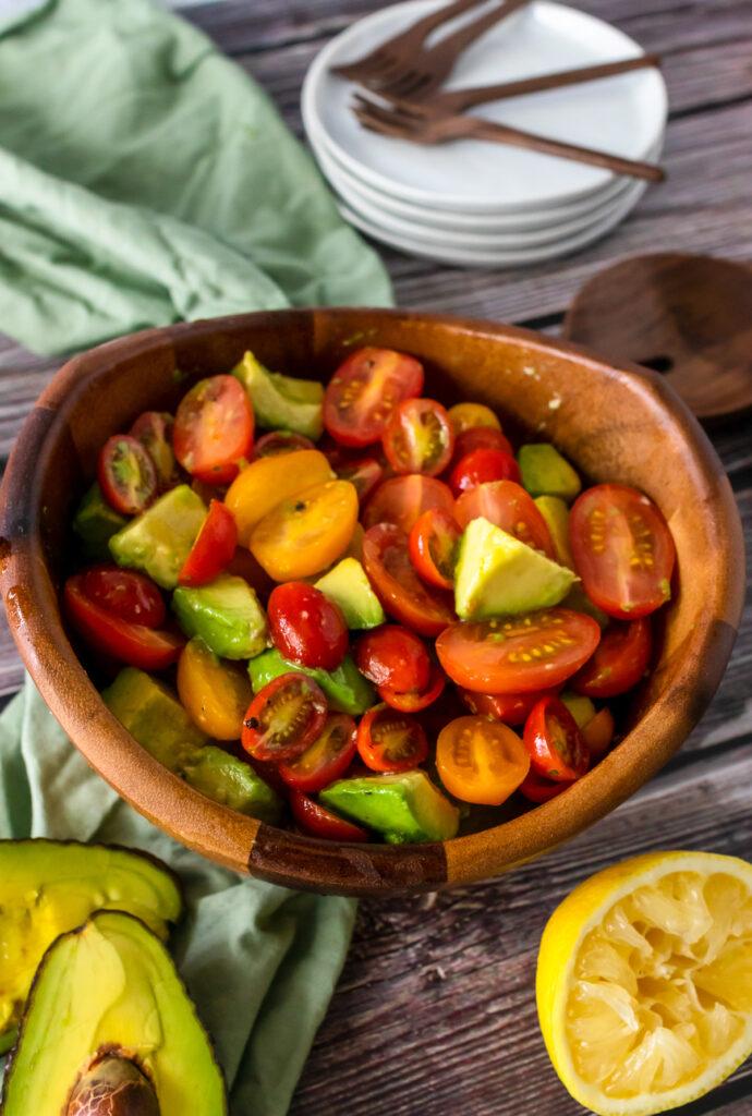 Avocado Tomato Salad in a wooden bowl ready to serve on white plates.