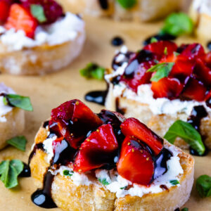 Strawberries and goat cheese with herbs on toast with balsamic drizzle.
