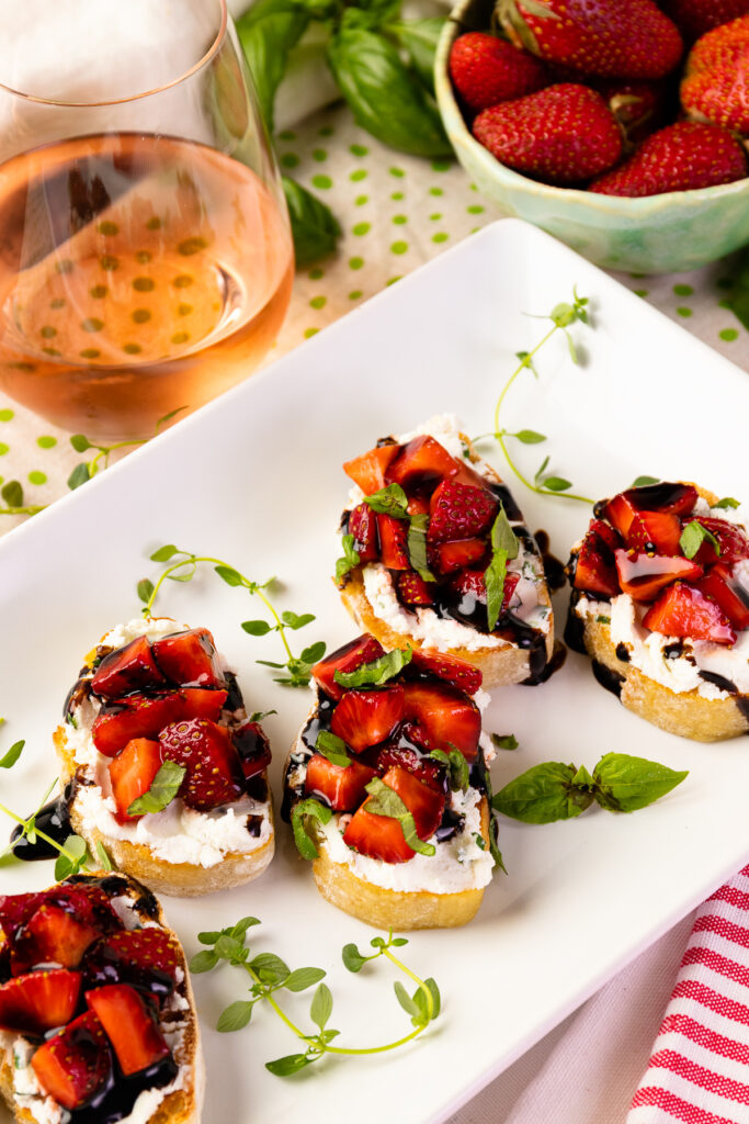 Strawberry Goat Cheese Bruschetta with rose wine on a whtie serving plate.