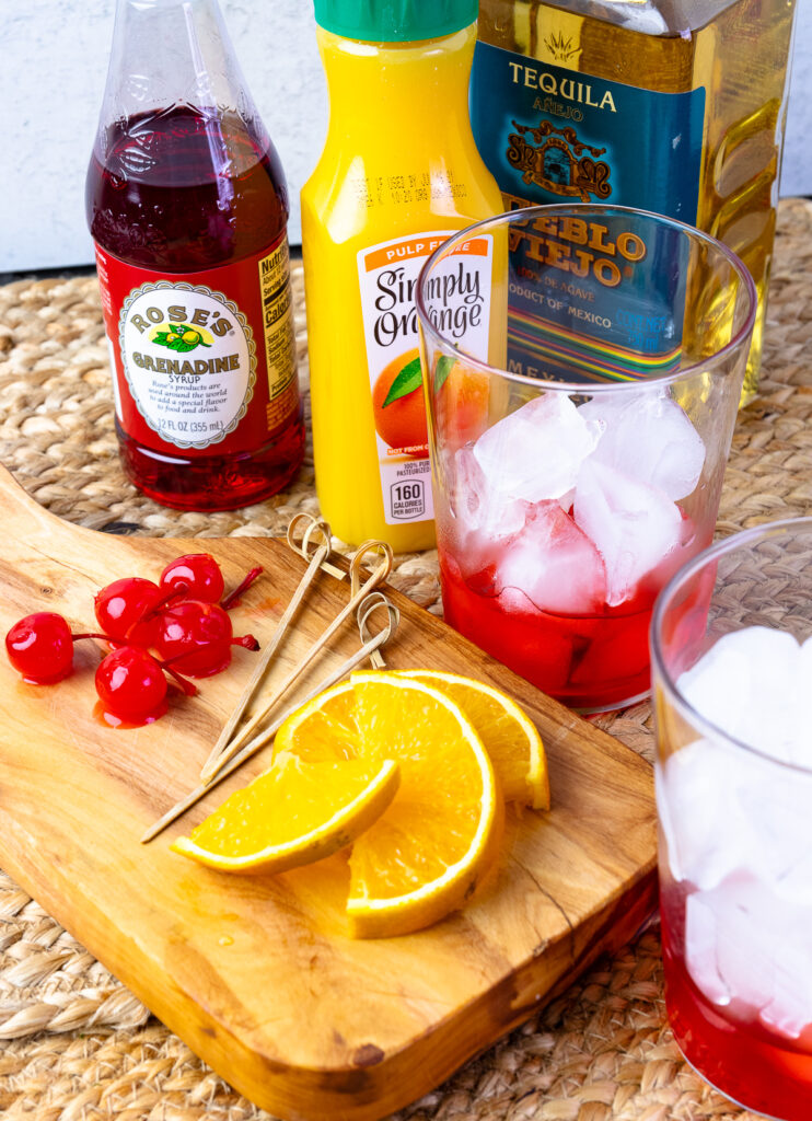 Sliced oranges and cherries with glasses for tequila sunrises.