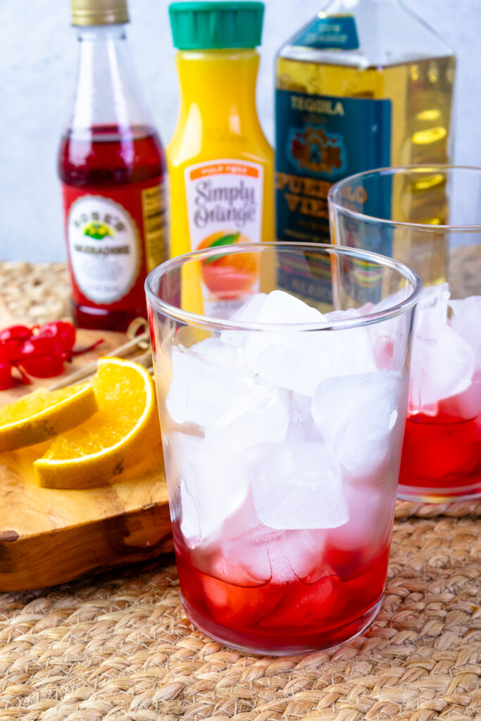 Glassses with ice and grenadine for Tequila Sunrises.