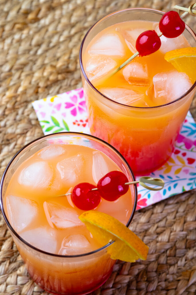 Refreshing Tequila Sunrise in a glass served over ice with pretty napkins.