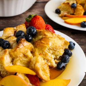French Toast Bread Pudding on a plate with peaches and berries.